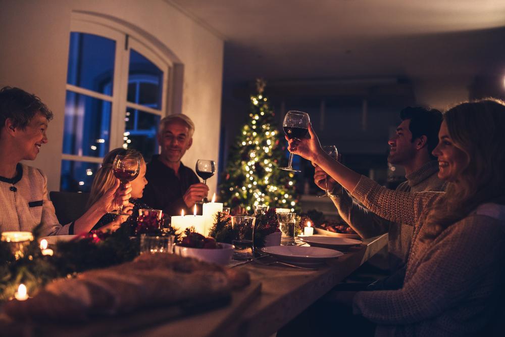 ロウソクの明かりが灯る自宅でワイン片手に家族とディナーを楽しんでいる