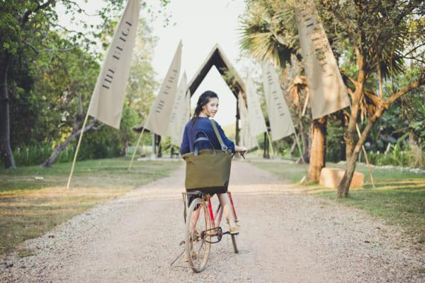 自転車に乗った女性が旅行バッグを持っている