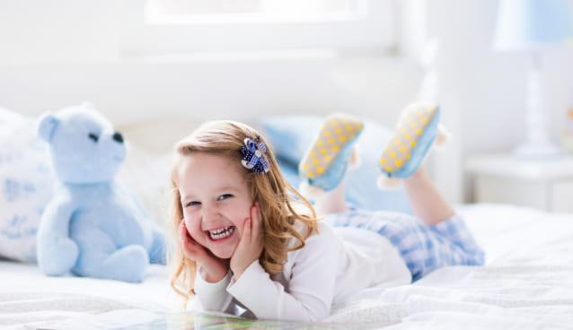 女の子がベッドの上で微笑んでいる