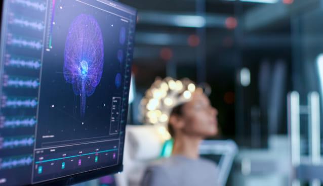 頭にヘッドセットをかぶった女性の脳の中がモニターに映っている