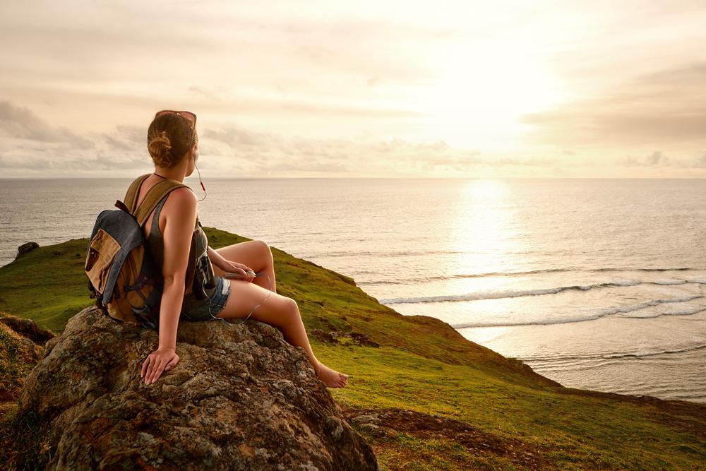 山頂でハイカーが夕日を眺めている
