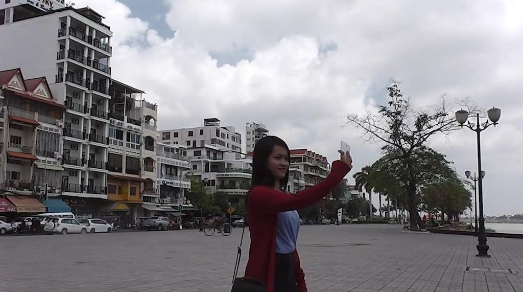 スマホで写真を撮るカンボジア女性
