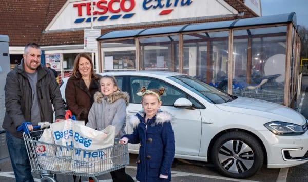 スーパーの駐車場で笑顔の家族