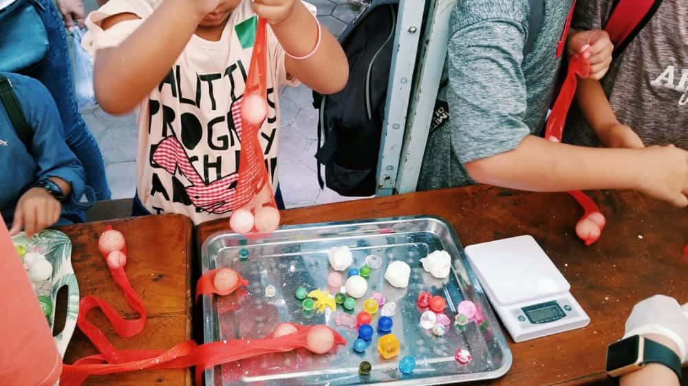 リサイクルした石鹸の中におもちゃを詰める子供たち。