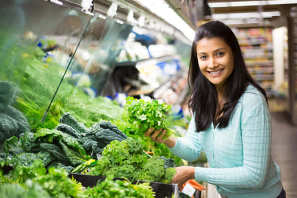 野菜の横で女の人が微笑む