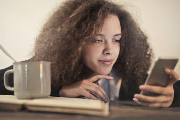 スマートフォンでライブ配信を見る女性