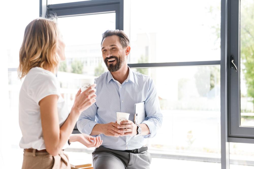 女性と男性が窓際でコーヒーを飲みながら談笑している