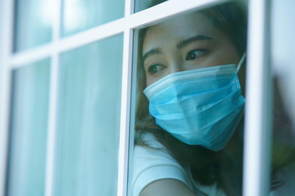 マスクをした人が窓から外を見つめている